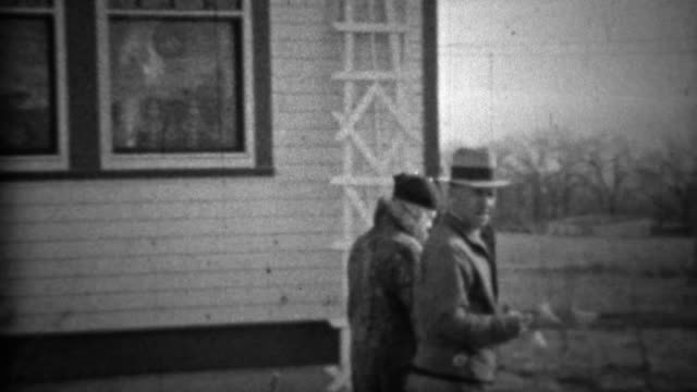 1933: Proud couple walking new farm property recently purchased. video