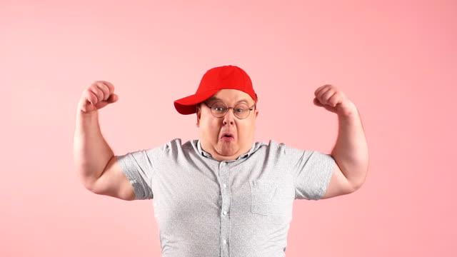 stolzer fanny fetter mann zeigt seinen willen und vertrauen in gesunde lifestyle-förderung, zeitlupe - held stock-videos und b-roll-filmmaterial