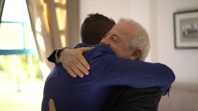 Proud father embracing his son and groom before weeding
