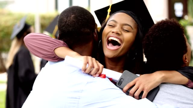 Proud female college graduate gives her parents a big hug Excited African American female college graduate embraces her parents after her college graduation. She has a big smile on her face as she hugs her parents. She is holding a diploma and smartphone. university stock videos & royalty-free footage