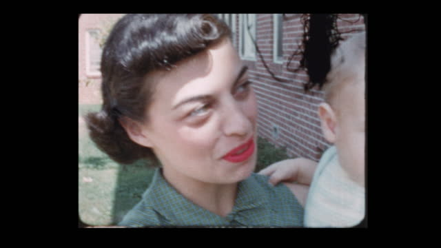 proud glam 50's mom holding infant baby in the air - neonati maschi video stock e b–roll
