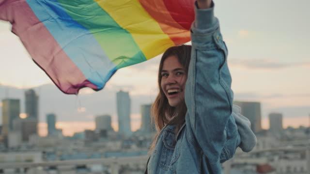 vídeos de stock, filmes e b-roll de lgbt orgulhoso. mulher feliz segurando bandeira lgbt. vista para o telhado - lgbt
