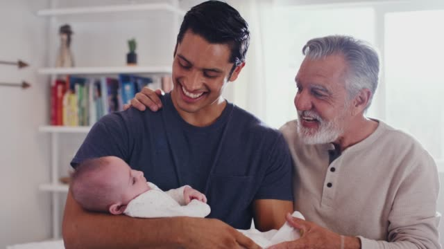 Proud Hispanic father holding his four month old son at home, with grandfather beside them, close up video