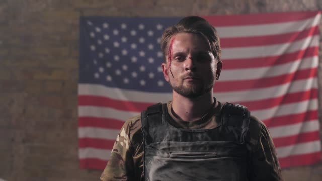 Proud injured soldier in helmet against US flag Portrait of wounded military man in bulletproof vest standing in front of stars and stripes of USA flag and taking off helmet. Patriot of United States of America posing on background of American flag camouflage clothing stock videos & royalty-free footage