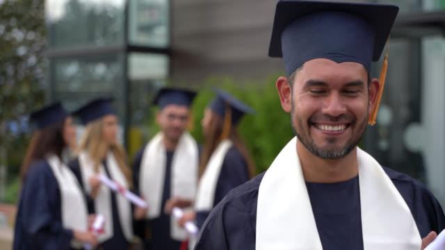 vídeos de stock, filmes e b-roll de estudante do sexo masculino orgulhosa segurando seu grau ao olhar muito animado graduar doutorado - beca