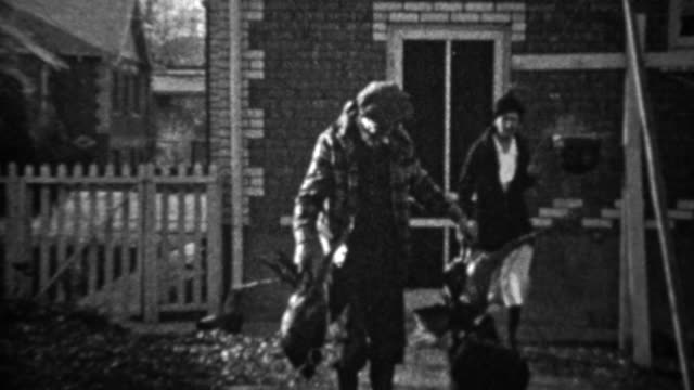 1935: Proud man shows dead pheasant birds in residential front porch. video