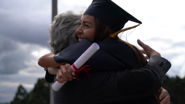 proud mba graduate hugging her dad celebrating after graduation ceremony - padre single video stock e b–roll