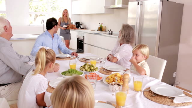 Proud mother bringing turkey to dinner table Proud mother bringing turkey to dinner table in the kitchen roast dinner stock videos & royalty-free footage