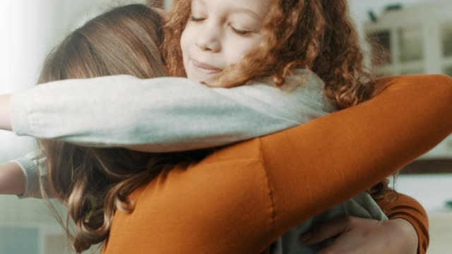 Proud mother hugging daughter Proud mother hugging daughter at home. hug stock videos & royalty-free footage