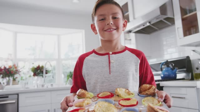 proud pre-teen hispanic boy standing in kitchen presenting the cakes heõs made to camera, close up - solo un bambino maschio video stock e b–roll