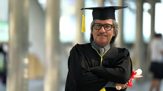 在戶外畢業典禮上, 穿著帽子和長袍的驕傲的高級成年男子。 - 文憑 個影片檔及 b 捲影像