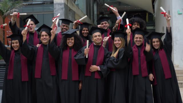 vídeos y material grabado en eventos de stock de orgulloso grupo exitoso de graduados universitarios sosteniendo su diploma con los brazos extendidos mirando a la cámara sonriendo - graduación