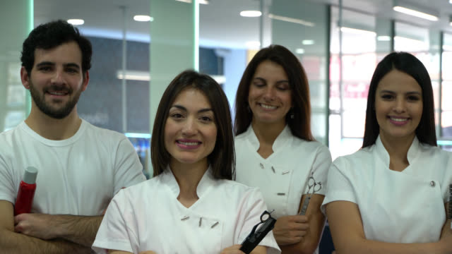 Orgulloso equipo de peluquería en un salón todos mirando a cámara sonriendo con los brazos cruzados - vídeo