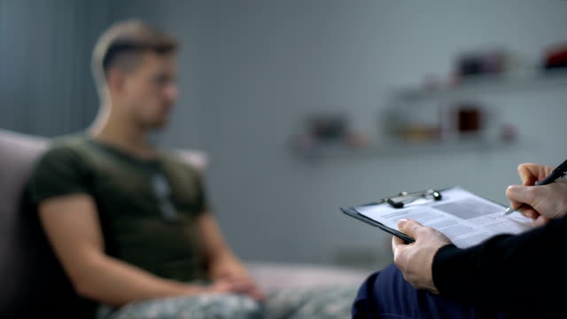 psychologist making notes during therapy session with sad male soldier, ptsd - fisioterapia video stock e b–roll