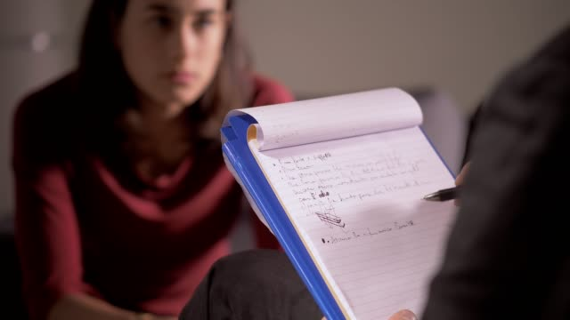 vidéos et rushes de psychologue prenant des notes pendant la session avec son patient féminin-close up - bloc note
