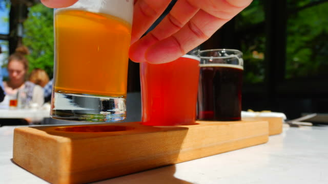 Pub Patio Restaurant with Beer Flight Taster Samples, Hand Holding Glass video