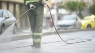 istock Public janitor deep cleaning the sidewalk and cycling lane with high pressure disinfectant solution in times of corona virus pandemic in a lockdown Bucharest, Romania 1226000389