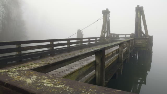 Public Pier, Fraser River Fog Fog, off the Fraser River, wraps around a pier in the early morning. British Columbia, Canada. fraser river stock videos & royalty-free footage