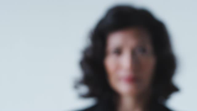 Pull Focus Portrait Of Smiling Mature Businesswoman In Suit Standing Against White Studio Wall