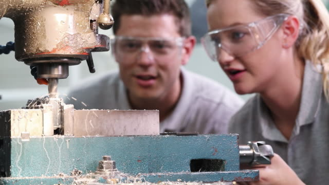 pull focus shot of engineer training female apprentice to use drill in factory - apprendista video stock e b–roll