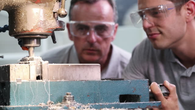 Pull Focus Shot Of Engineer Training Male Apprentice To Use Drill In Factory Pull Focus Shot Of Engineer Training Male Apprentice To Use Drill In Factory quality control stock videos & royalty-free footage