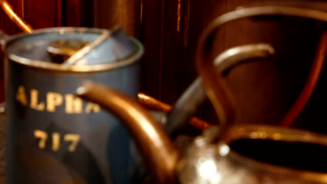 pull focus shot of two vintage oil buckets next to a working steam engine - stile del xix secolo video stock e b–roll