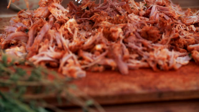 Pulled pork on a vintage wooden board looking deliciously tender tender shredded pork being pulled apart on a vintage wooden board with herbs nearby in preparation for pulled pork sandwiches pork stock videos & royalty-free footage