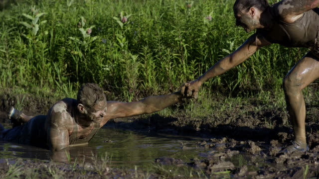 Pulling Friend Out Of Mud A group of adults are participating in a mud run. A male adult is standing and helping a female adult up out of the mud. conquering adversity stock videos & royalty-free footage