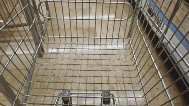Pulling shopping trolley at a supermarket - POV Pulling shopping trolley at a supermarket - POV market retail space stock videos & royalty-free footage