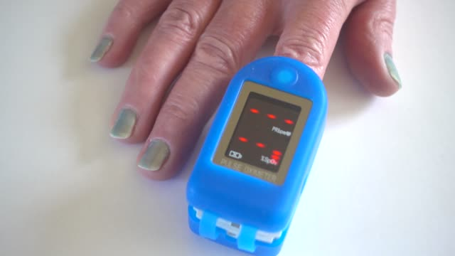 Pulse oximeter on finger being used to test blood oxygen level in case of virus infection of the lungs on senior mans hand Pulse oximeter on finger being used to test blood oxygen level in case of virus infection of the lungs on senior mans hand medical oxygen equipment stock videos & royalty-free footage
