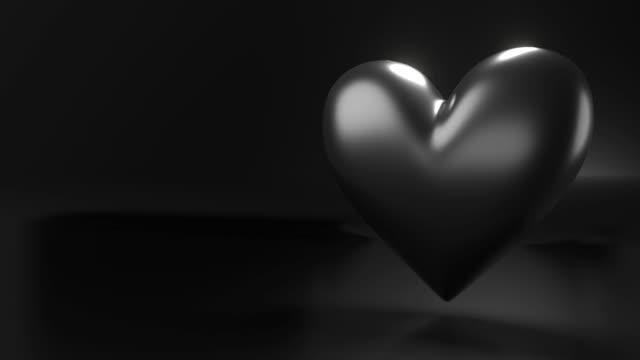 Pulserend zwart hartvormobject op zwarte tekstruimte. video