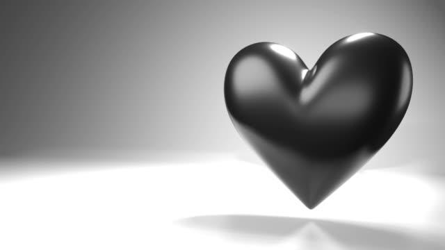 Pulserend zwart hartvormvoorwerp op witte tekstruimte. video