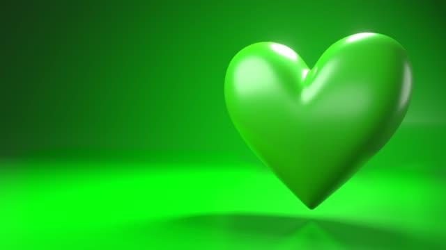 Pulserend groen hartvormvoorwerp op groene tekstruimte. video