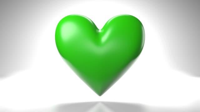 Pulserend groen hartvormvoorwerp op witte achtergrond. video