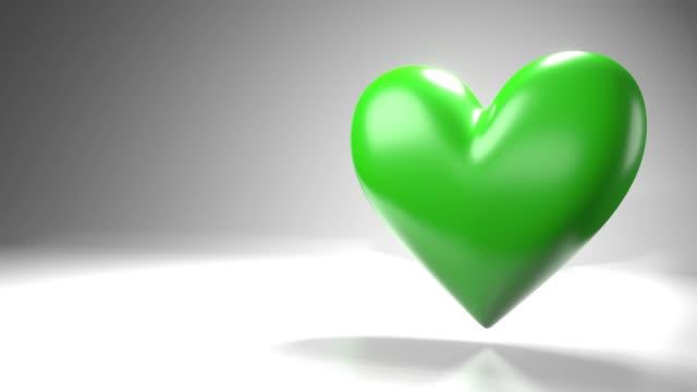 Pulserend groen hartvormvoorwerp op witte tekstruimte. video