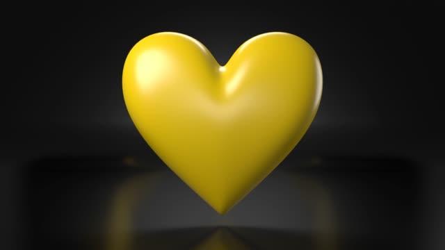 Pulserend geel hartvormvoorwerp op zwarte achtergrond. video