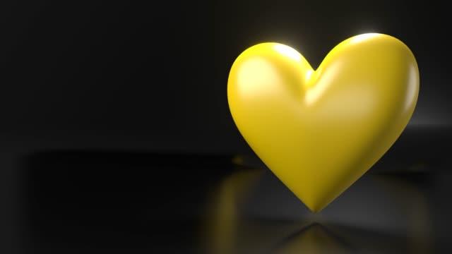 Pulserend geel hartvormobject op zwarte tekstruimte. video