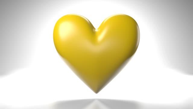Pulserend geel hartvormvoorwerp op witte achtergrond. video