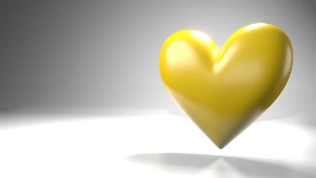 Pulserend geel hartvormvoorwerp op witte tekstruimte. video