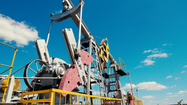 pump jacks stand on oil field against sky low angle shot