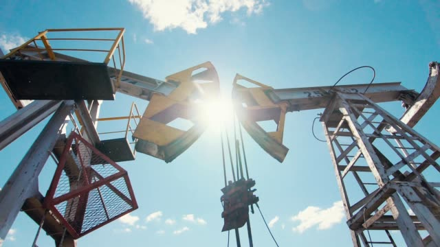 pumpjacks on oil field against blue sky with white clouds