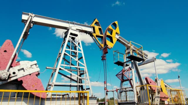 pumpjacks operate on oil field against sky with white clouds