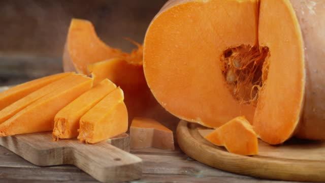 pumpkin slices on a cutting board with cool steam. - zucca legenaria video stock e b–roll