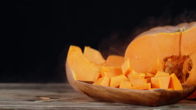 Pumpkin slices on a wooden plate with a cool steam.