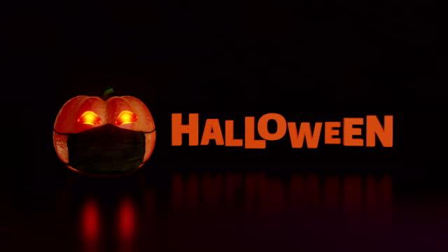 Pumpkin wears black mask and rolls in revealing the word Halloween. Animation of orange pumpkin and the Halloween word. halloween covid stock videos & royalty-free footage