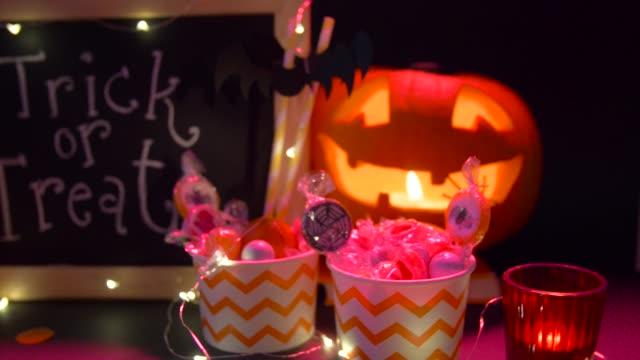kürbisse, bonbons und halloween-dekorationen - girlande dekoration stock-videos und b-roll-filmmaterial