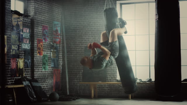 punching bag crunches. strong masculine man embrassing the bag with his legs and pumping his abs and core muscles. handsome male trains in a gym and falls in the end. sport accident causing back pain. - sacco per il pugilato video stock e b–roll