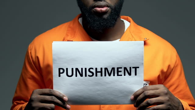 Punishment word on cardboard in hands of Afro-American prisoner, death penalty Punishment word on cardboard in hands of Afro-American prisoner, death penalty civil rights stock videos & royalty-free footage