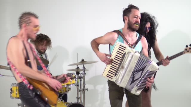 Punk rock band. Shooting a clip. Musicians are jumping with instruments. The bass player is dressed in a women's dress and wig. In the frame, a balalaika and a drummer.