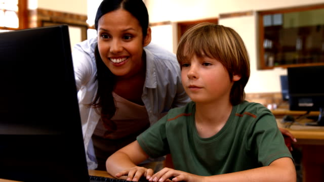 Pupil and teacher in computer class at school video